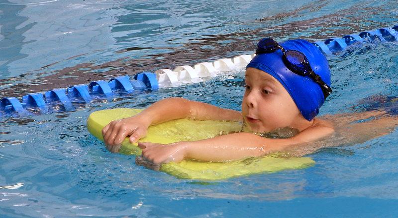 Ett barn som simmar genom att hålla i en simdyna.