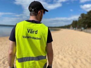 """Bilden visar en man som står på stranden i Varamobaden. Mannen har en gul varselväst med texten """"Värd Varamobaden"""" på ryggen."""